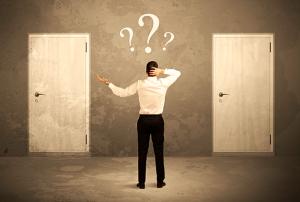 Homem parado diante de duas portas iguais. Sobre sua cabeça, flutuam pontos de interrogação. A imagem ilustra a dúvida entre falsos amigos e falsos cognatos, termos parecidos para coisas diferentes.